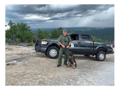 K-9, handler, and truck on top of Stone Mountain