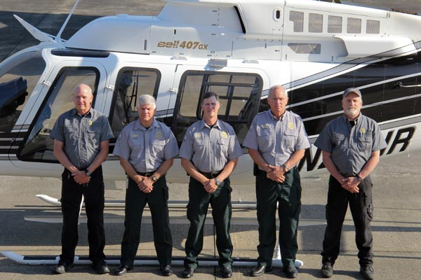 Image of five members of the Aviation Unit standing in front of a helicopter