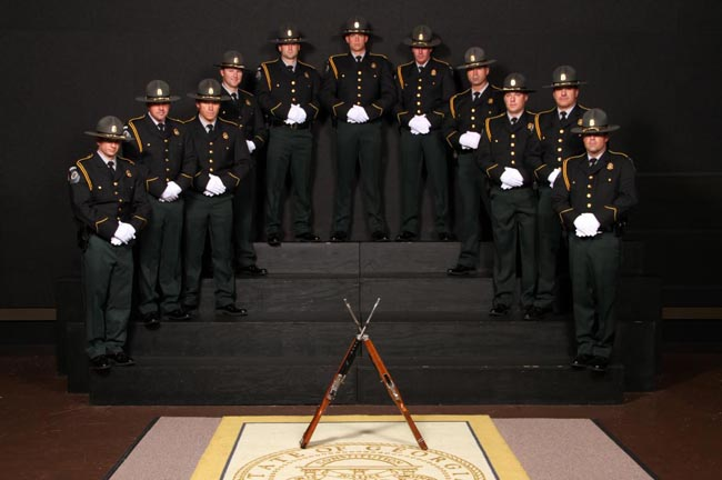 Image of eleven members of the Honor Guard with crossed rifles
