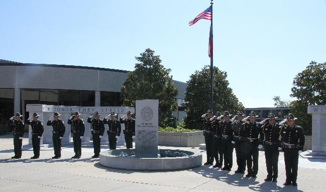 Image of fourteen members of the Honor Guard saluting at outdoor memorial