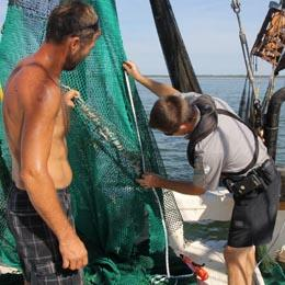 Image of a Ranger examining a fisherman's nets