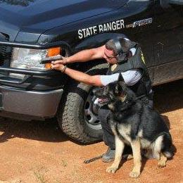 Image of a Ranger and his K9 crouching behind a Law Enforcement vehicle